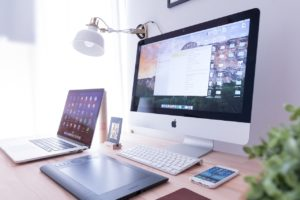 mac desktop and laptop screens on desk